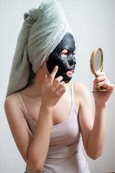 Mooie vrouw met zwart gezichtsmasker, levensstijl concept
