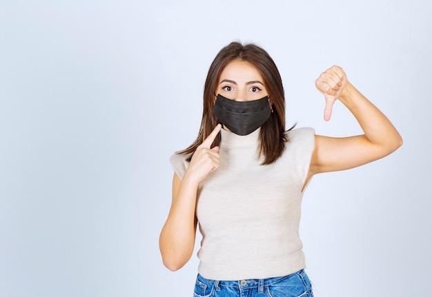 Mooie vrouw met zwart medisch masker met een duim naar beneden.