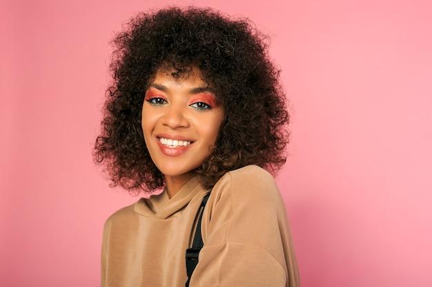 Mooie vrouw met zwarte huid en stijlvol afrikaans kapsel in sportieve outfit poseren op roze