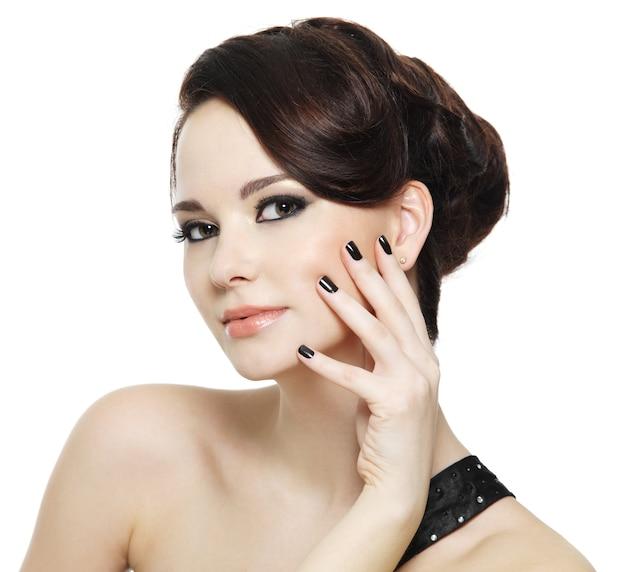 Mooie vrouw met zwarte nagels en heldere oogsamenstelling op wit