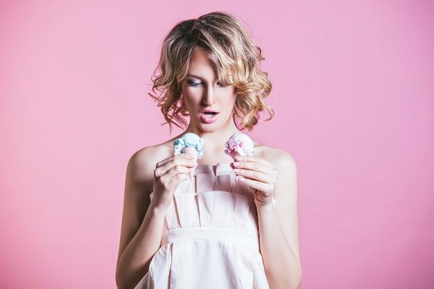 Mooie vrouw model blonde met consumptie-ijs en make-up mode op een roze achtergrond in studio Premium Foto