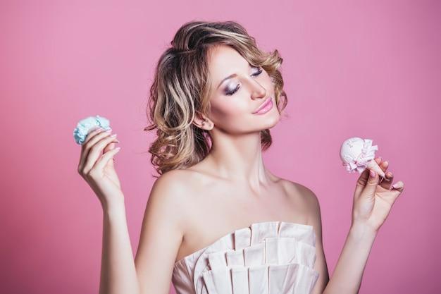 Mooie vrouw model blonde met consumptie-ijs en make-up mode op een roze achtergrond in studio
