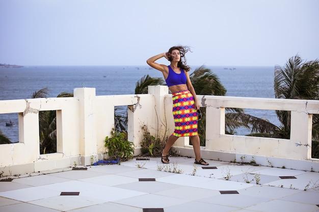 Mooie vrouw model modieus en sexy op het balkon met uitzicht op de zee en de palmbomen