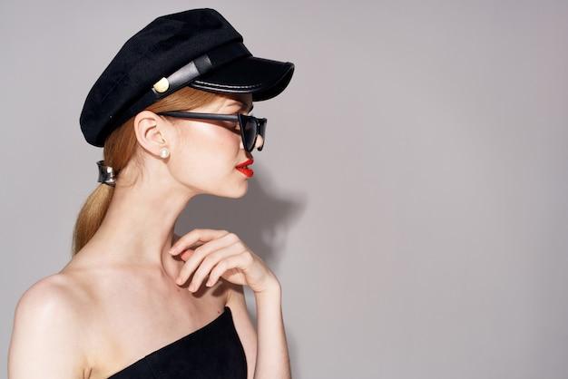 Mooie vrouw modieuze kleding donkere glazen rode lippen avondjurk.