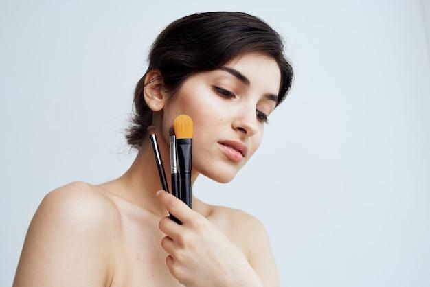 Mooie vrouw naakt schouders make-up borstel cosmetica huidverzorging