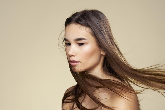 Mooie vrouw naakte schouders cosmetica schone huid haarverzorging beige achtergrond