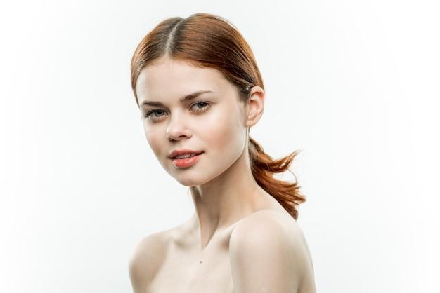 Mooie vrouw naakte schouders cosmetica verzameld haar aantrekkelijk uiterlijk