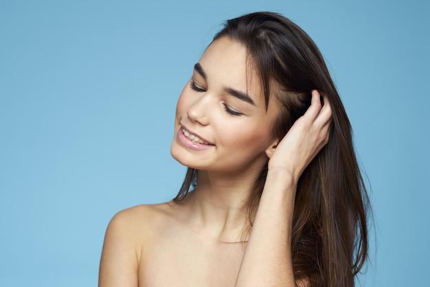 Mooie vrouw naakte schouders haarverzorging close-up bank blauwe achtergrond