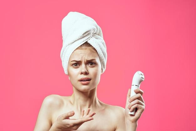 Mooie vrouw naakte schouders handdoek op hoofd gezicht massage roze.