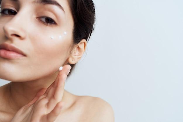 Mooie vrouw naakte schouders schone huid geldt crème op gezicht