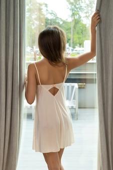Mooie vrouw naast een raam in de ochtend