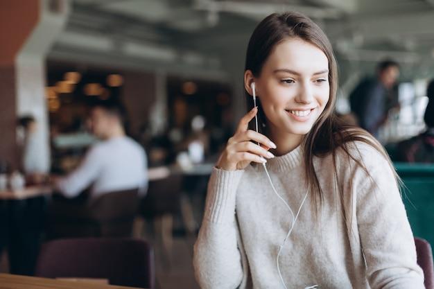 Mooie vrouw natuurlijke gezicht close-up casual vrouwelijke portret levensstijl schoonheid meisje met smartphone in café