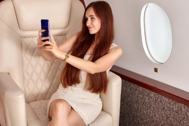 Mooie vrouw neemt foto's van zichzelf aan boord van een privéjet.