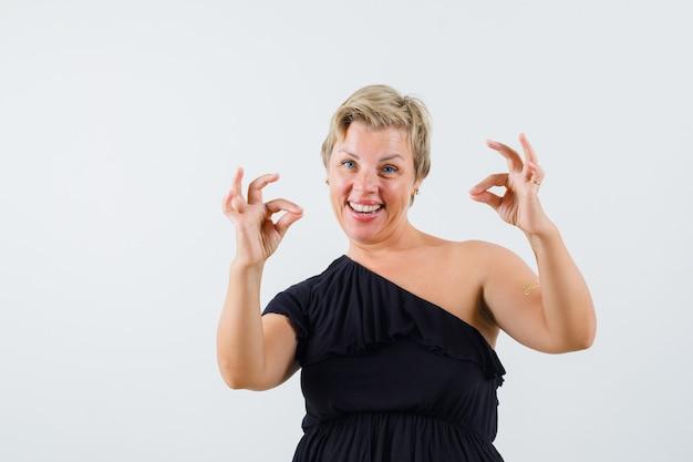 Mooie vrouw ok gebaar in zwarte blouse tonen en vrolijk kijken