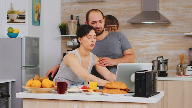 Mooie vrouw online winkelen via internet tijdens het ontbijt met man, betalen met creditcard. informatie invoeren, klant die e-commercetechnologie gebruikt om dingen op internet te kopen, cosumerismebankieren