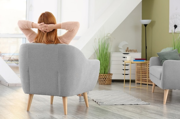 Mooie vrouw ontspannen in fauteuil thuis at