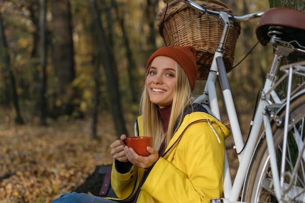 Mooie vrouw ontspannen in herfst bos, kopje koffie te houden, op zoek