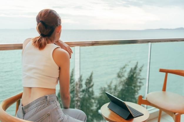 Mooie vrouw ontspannen op het terras van het hotel met uitzicht op de oceaan in de zomer