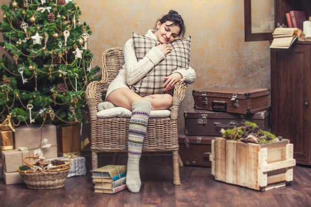 Mooie vrouw ontspannen zittend in een stoel met kussens in het kerstinterieur