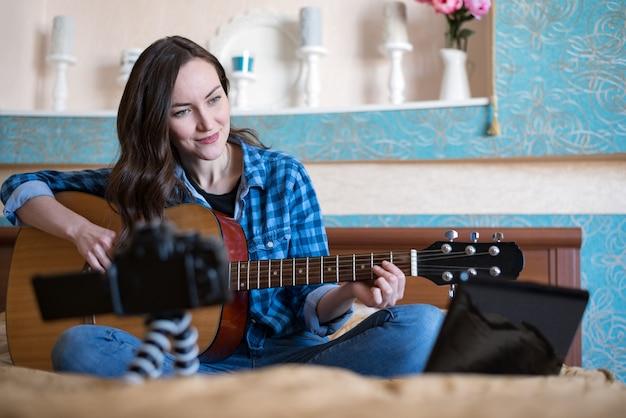 Mooie vrouw op bed in de slaapkamer, neemt muziekblog op en speelt akoestische gitaar
