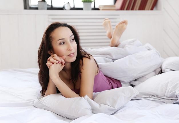Mooie vrouw op bed