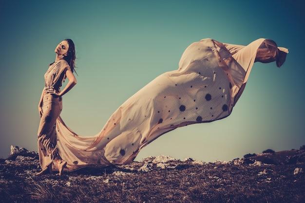 Mooie vrouw op de rots in licht weefsel