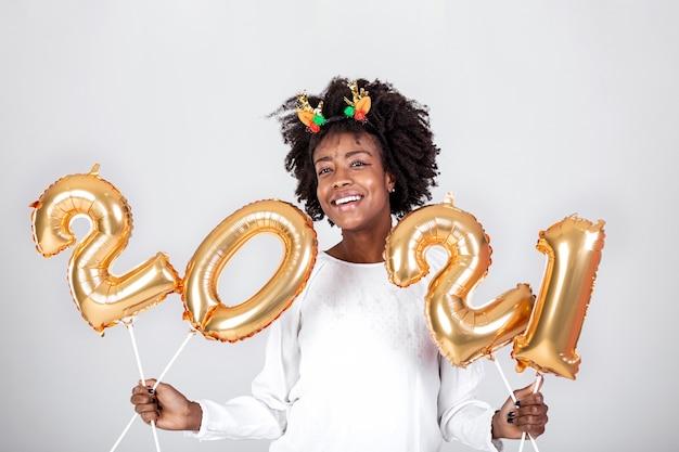 Mooie vrouw op een nieuwjaarsfeest: spelen met gouden ballonnen nummers 2021