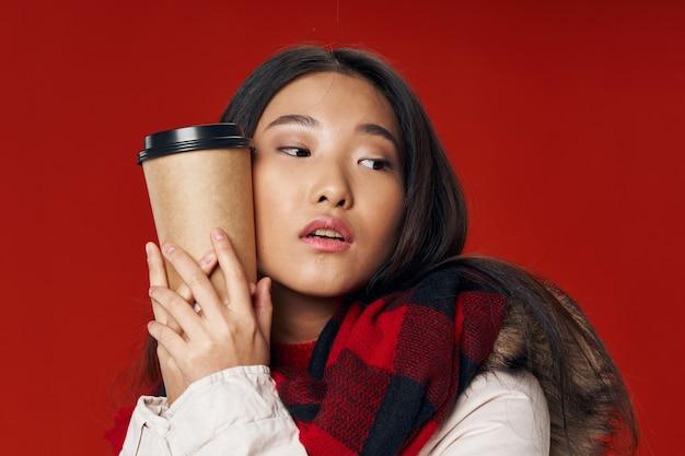 Mooie vrouw op een rode knuffels een kopje koffie