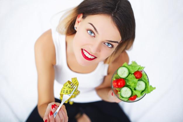 Mooie vrouw op gezond dieet met organische groene groentesalade in keuken.