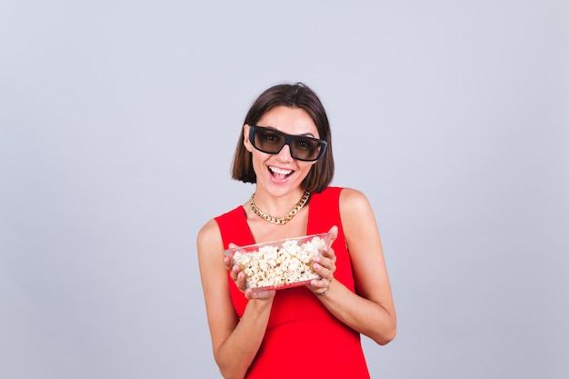 Mooie vrouw op grijze muur in 3d-bioscoopbril met popcorn, vrolijke gelukkige positieve emoties