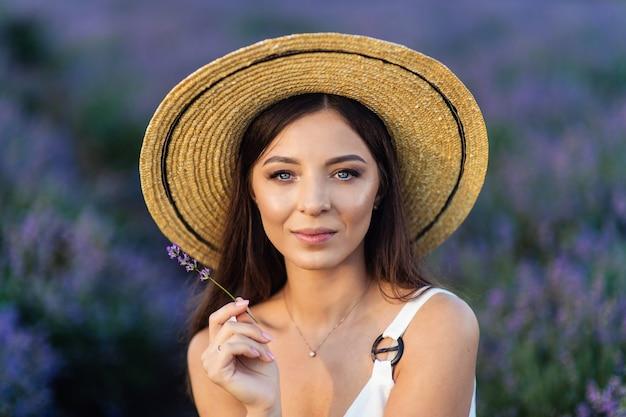 Mooie vrouw op het lavendelveld op zonsondergang. fantastische zomerse stemming.