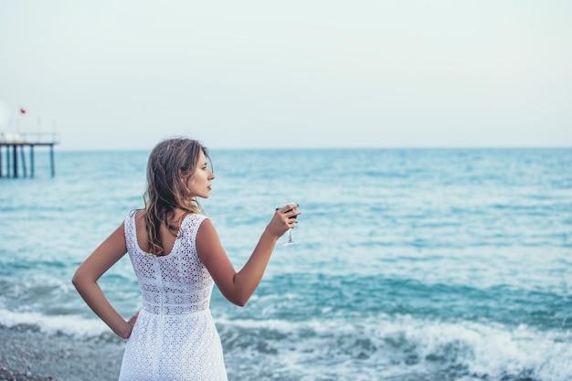 Mooie vrouw op het strand met een glas wijn in witte jurk ontspant gelukkig