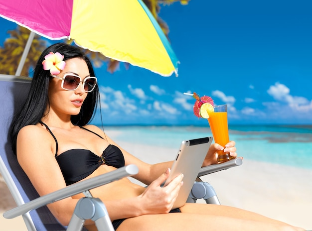 Mooie vrouw op het strand met ipad.
