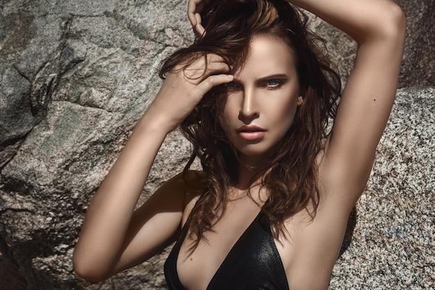 Mooie vrouw op het strand met rotsen