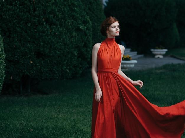 Mooie vrouw op luxe aantrekkelijk uiterlijk rode jurk park