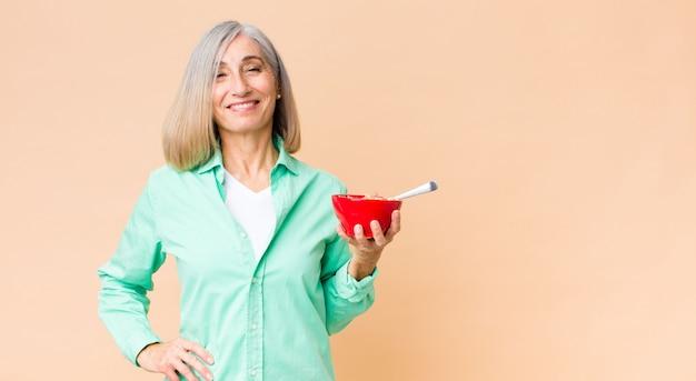 Mooie vrouw op middelbare leeftijd met een ontbijtkom