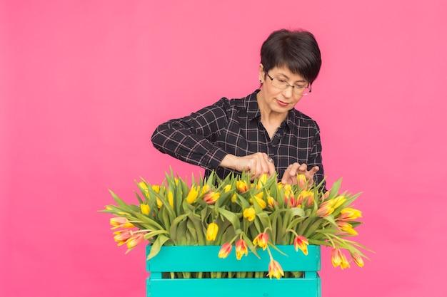Mooie vrouw op middelbare leeftijd met gele tulpen op roze achtergrond. floristiek, vakantie en geschenken concept