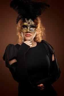 Mooie vrouw op middelbare leeftijd met rood haar in een carnaval-masker. bruine muur