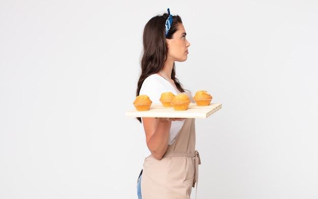 Mooie vrouw op profielweergave denken, fantaseren of dagdromen en een dienblad met muffins vasthouden