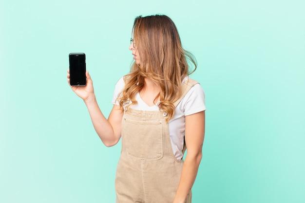 Mooie vrouw op profielweergave denken, fantaseren of dagdromen en een smartphone vasthouden
