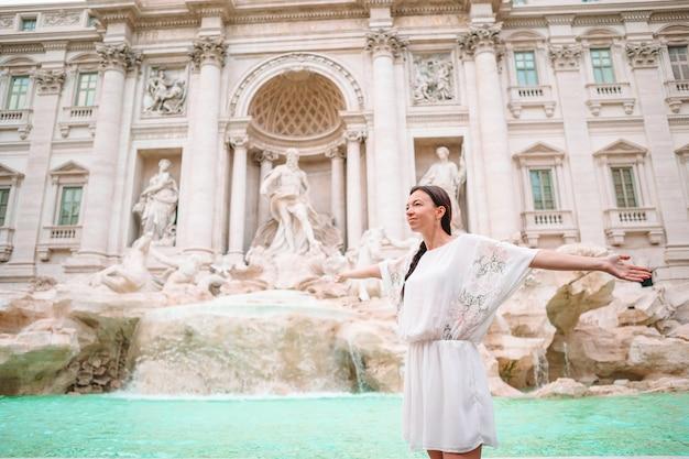Mooie vrouw op zoek naar de fontein van trevi tijdens haar reis in rome, italië.
