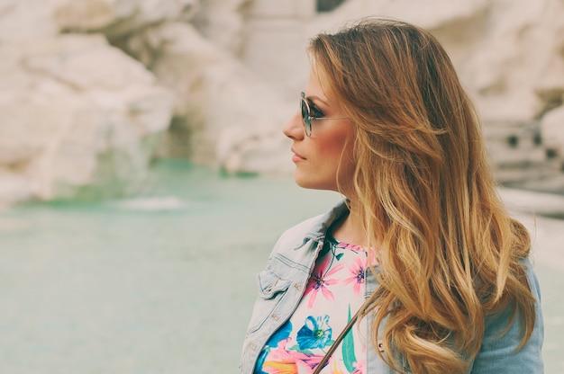 Mooie vrouw op zoek naar de fontein van trevi tijdens haar reis in rome