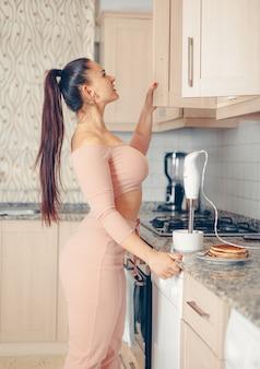 Mooie vrouw op zoek naar iets in de keuken in zalmroze crop top en broek
