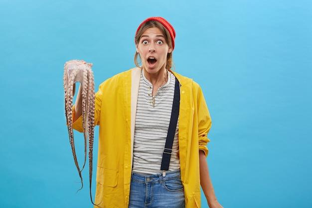 Mooie vrouw op zoek verrast terwijl ze octopus vasthoudt