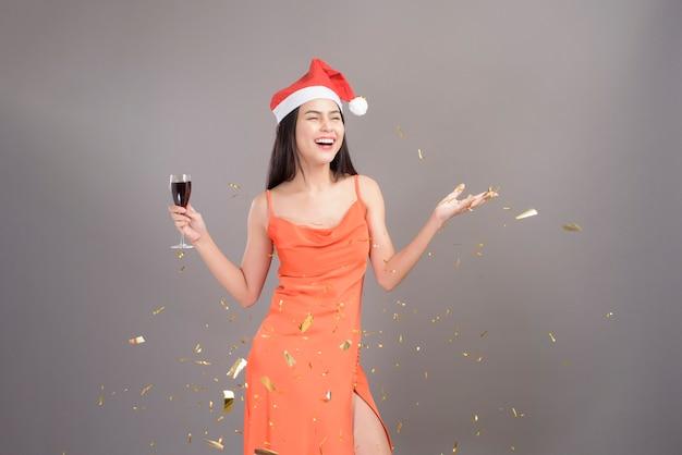 Mooie vrouw oranje jurk met glas champagne en kerstmuts dragen