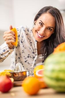 Mooie vrouw perst sinaasappel met fruit op tafel.