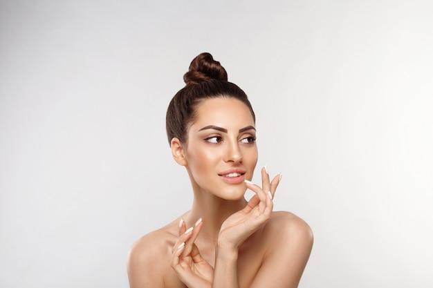Mooie vrouw portret, huid zorg concept, huidverzorging. dermatologie. portret van vrouwelijke handen met manicurespijkers wat betreft haar gezicht.