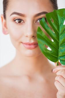 Mooie vrouw portret op witte achtergrond met schone huid en groen blad in de hand