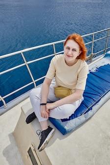 Mooie vrouw poseert voor fotograaf aan boord van een jacht voor rondleidingen