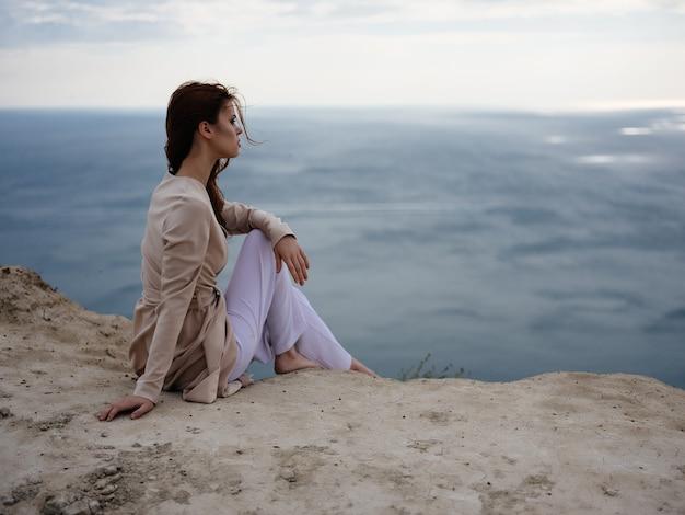 Mooie vrouw poseren in de buurt van rotsen in de elegante stijl van het zand